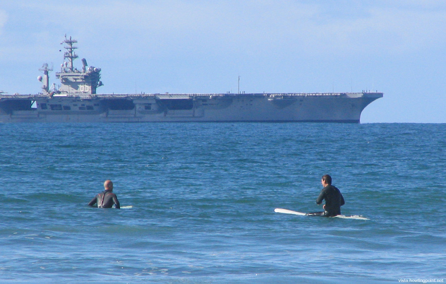 The Uber Lifeguard: Surfers at Coronado City Beach watch the carrier Nimitz (CVN 68) as she returns to San Diego Bay.